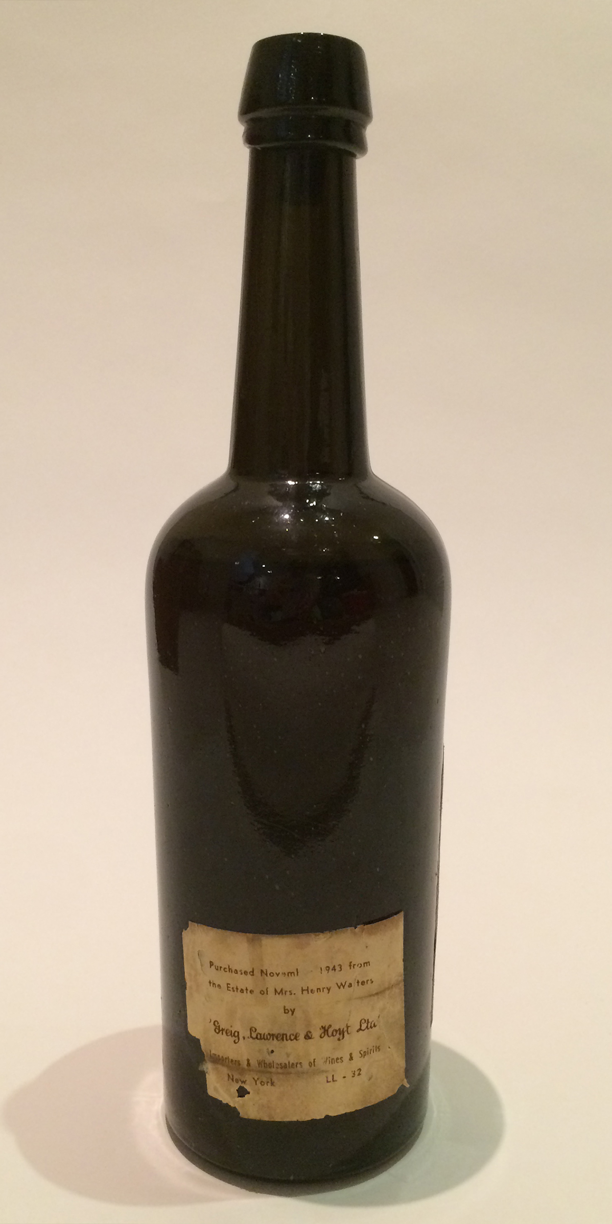 Back side of Baker's 1847 bottle showing Greig sale labe affixed in 1943.