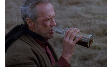 Clint Eastwood as Will Munny drinks from a whiskey bottle.